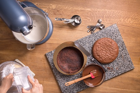 chocolate biscuit: chocolate cake baking ingredients on wooden kitchen table with kitchenware, top view Stock Photo