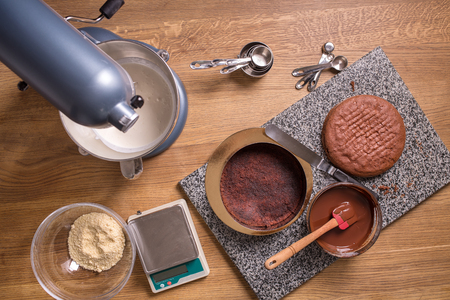 biscuits: chocolate cake baking ingredients on wooden kitchen table with kitchenware, top view Stock Photo