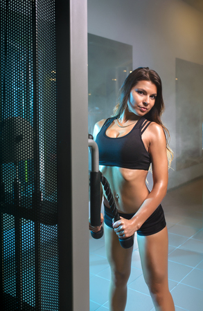 musculation: young fitness woman working out training with crossover in gym, horizontal photo