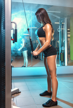 young fitness woman working out training with crossover in gym, horizontal photo