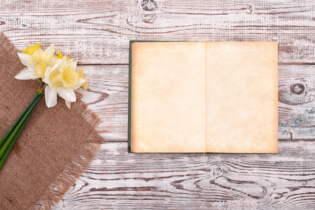 Blank notebook with flower on old vintage wooden table background top view
