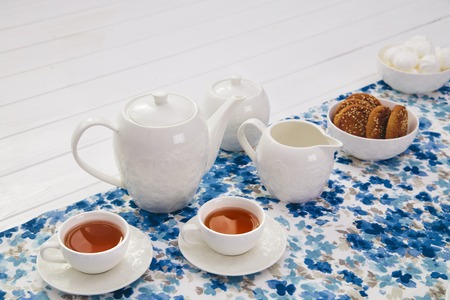 cups of tea with milk, cream and biscuits on wooden white table Stok Fotoğraf