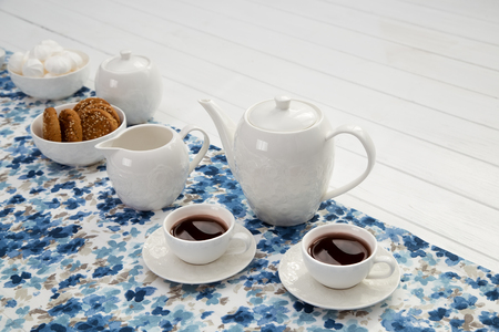 cups of coffee with milk, cream and biscuits on wooden white table Stok Fotoğraf