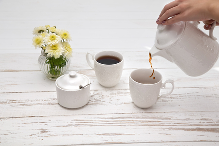 hands pours tea in cup of tea on wooden white table