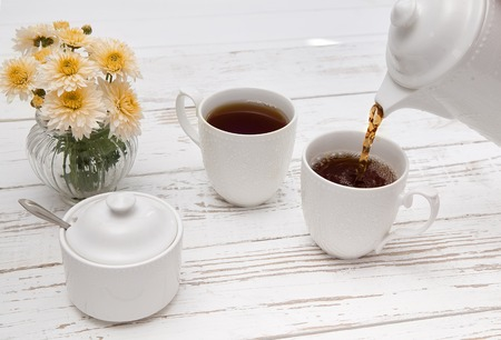 pours tea in cup of tea on wooden white table