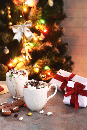 hot chocolate with marshmallow on table with christmas tree lights background Stok Fotoğraf