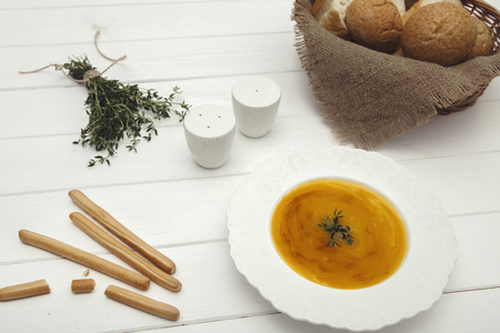 Dietary vegetarian pumpkin cream soup puree on a light wooden table in a white plate. Top view. Stok Fotoğraf