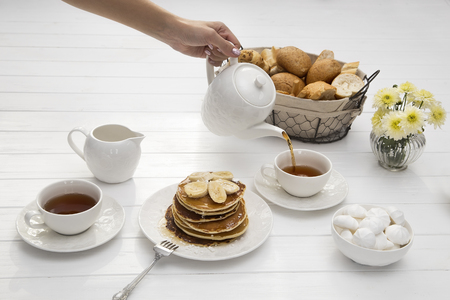 breakfast with pancakes and tea on table