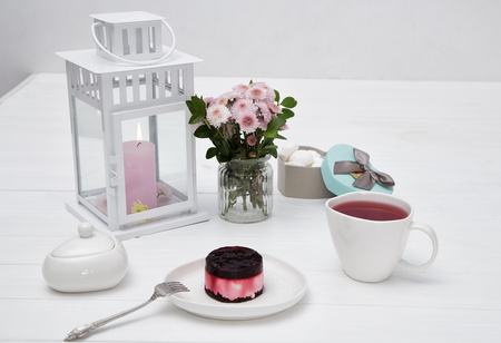 tea set and a bouquet of flowers on a white table, tea