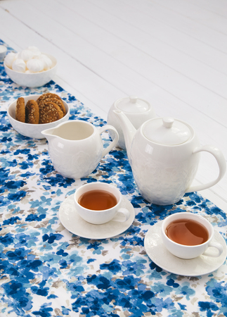 cups of tea with milk, cream and biscuits on wooden white table background with copyspace
