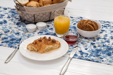 Continental breakfast with fresh croissants, bread, biscuits, jam and orange juice on table, selective focuse.