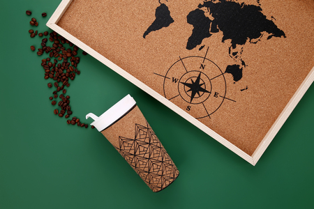 flatlay coffee cup with coffee beans and map on green background copy space