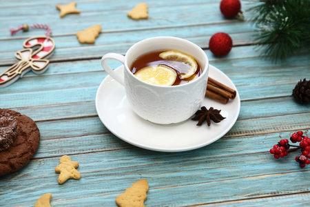Cup of tea and cookies, pine branches, cinnamon sticks, anise stars on table. Christmas, winter concept. Flat lay top view.