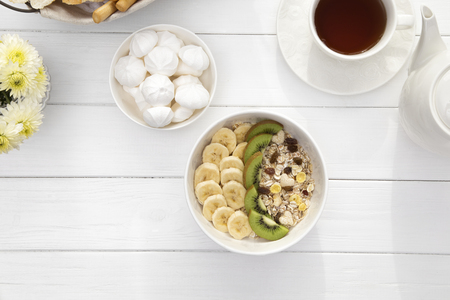Breakfast with oatmeal porridge, coffee cup and fruits. Oatmeal with kiwi and banana. Healthy breakfast concept. Top view