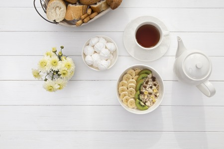 Breakfast with oatmeal porridge, tea cup and fruits. Oatmeal with kiwi and banana. Healthy breakfast concept. Top view Stok Fotoğraf