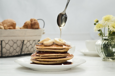 Woman pouring honey onto tasty pancakes with bananas on table, closeup