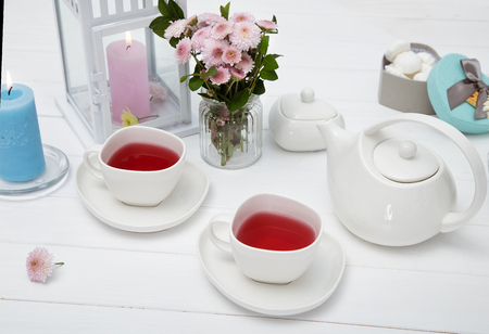 cups of fruit tea on wooden white table decorated with flowers Stok Fotoğraf
