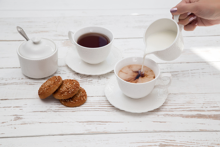 female hands pours cream in cup of tea on wooden white table background with copyspace