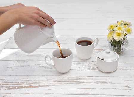 female hands pours tea in cup of tea on wooden white table background with copyspace