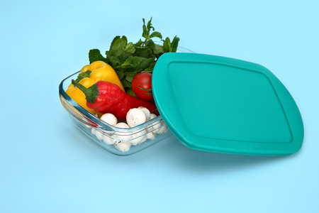 Plastic container with fresh vegetables on blue background Фото со стока