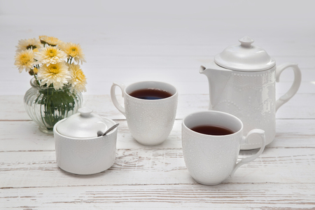 teatime cups of tea on white wooden table background with copyspace