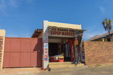 ohannesburg , Gauteng  South Africa -August 02 2018 : small Spaza African shop, showing variety of goods for sale, hot daytime, blue sky in the background, man inside the store, horizontal shot