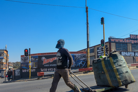 johannesburg , Gauteng / South Africa -August 02 2018 : African male waste picker working , large carry bag with recyclables, daytime on the streets ,horizontal shot, walking to destination, 新聞圖片