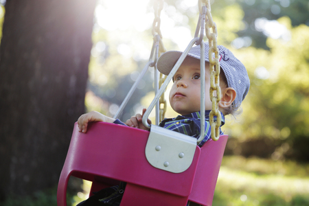 Cute little boy having fun on a swing outdoor in the park on sunset Banque d'images