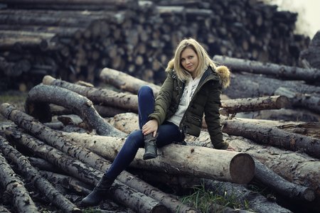 Attractive girl sits on a tree trunks. spend the morning in the garden, looking at the camera