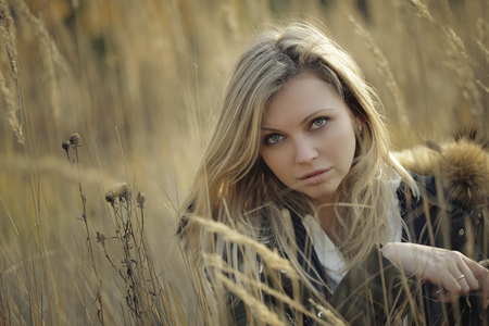 Portrait of beautiful young woman with makeup in high grass looking at the camera Фото со стока