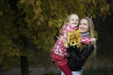 Young beautiful mother holds her litle girl in autumn park looking at the camera