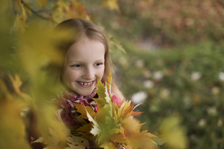 Portrait of a Happy smiling little girl in the autumn park. Cute four years old child enjoying nature outdoors. Banque d'images