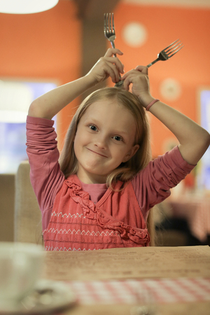little girl is holding forks over her head at the restaurant Banque d'images