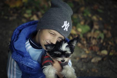 Portrait of Little kid boy with biewer terrier dog, in the park
