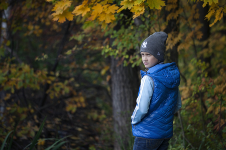 Boy wearing coat and a cap, looking over his shoulder in the autumn park