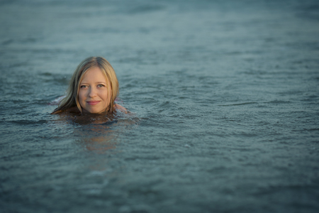 Girl enjoying bathing in a blue water Banque d'images