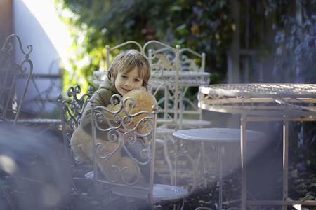 Little boy with a teddy bear sitting on the chair