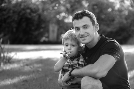 Portraits of happy european family of two people having fun outside in beautiful summer or spring green field. Dad is sitting with his little funny son and enjoys nature looking at the camera Black & White