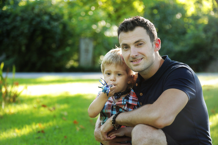 Portraits of happy european family of two people having fun outside in beautiful summer or spring green field. Dad is sitting with his little funny son and enjoys nature looking at the camera Banque d'images