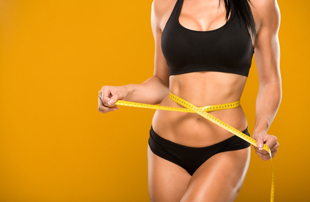 slim tummy: beautiful fitness model measures the waist on a yellow background Stock Photo
