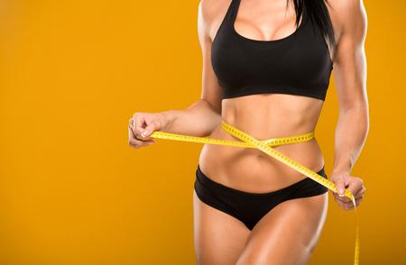 mujeres fitness: modelo de la aptitud hermosa mide la cintura sobre un fondo amarillo