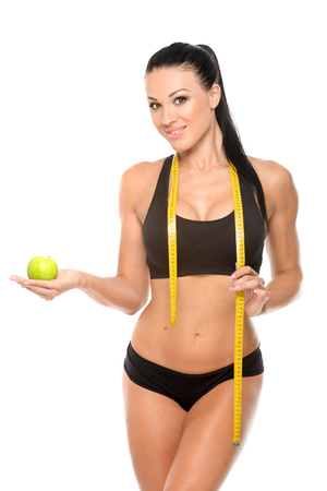 obese woman: Beautiful fitness model with apple and measuring tape on a white background isolate