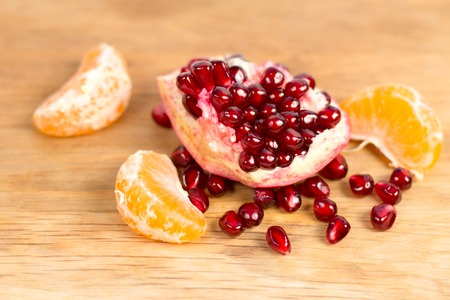 losing control: tangerine and pomegranate on a wooden stand Stock Photo
