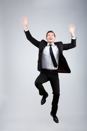 formals: portrait of a businessman jumping for joy on a gray background