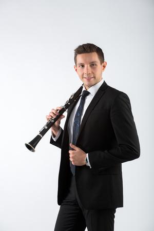 clarinete: el joven músico sobre un fondo gris toca el clarinete Foto de archivo