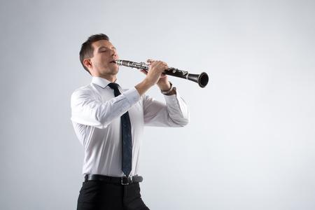 clarinete: el joven m�sico sobre un fondo gris toca el clarinete Foto de archivo