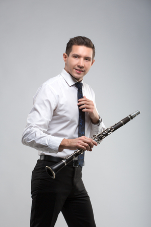clarinete: the young musician on a gray background plays the clarinet