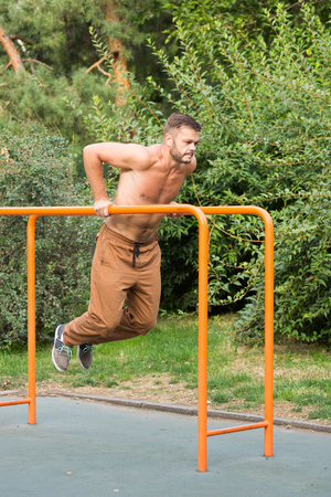 fitness, sport, exercising, training and lifestyle concept - young man doing triceps dip on parallel bars outdoors Stock Photo