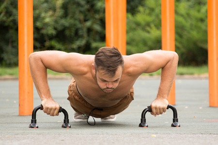 grapple: Push-ups - man fitness model training pushups outdoors. Fit male fitness trainer working out exercising in summer