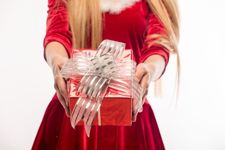 Young woman dressed as Santa holding a gift box on a white background. isolate Stock Photo